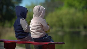 Two little child look a the lake view. Outdoors stock footage
