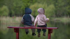 Two little child look a the lake view. Outdoors stock video footage