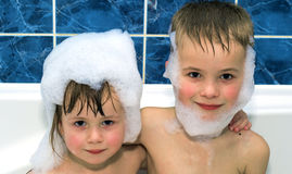 Two little children in a bathtub with shampoo foam Royalty Free Stock Photo