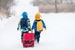Two little children, boy brothers with backpacks and a big red s Royalty Free Stock Photos