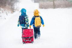 Two little children, boy brothers with backpacks and a big red s Stock Photo
