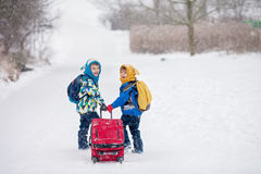 Two little children, boy brothers with backpacks and a big red s Royalty Free Stock Photo