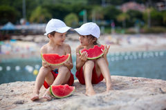 Two little children, boy brothers, eating watermelon on the beac Stock Photography