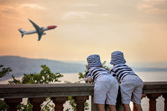 Two little children, boy brothers, looking at landing airplane i Royalty Free Stock Photo