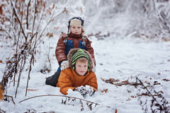 Two little children, boy brothers playing and lying in snow outdoors during snowfall. Active leisure with children in winter on co Royalty Free Stock Image