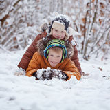 Two little children, boy brothers playing and lying in snow outdoors during snowfall. Active leisure with children in winter on co Stock Photo