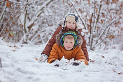 Two little children, boy brothers playing and lying in snow outdoors during snowfall. Active leisure with children in winter on co Royalty Free Stock Images