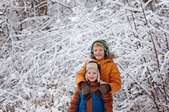 Two little children, boy brothers playing outdoors during snowfall. Active leisure with children in winter on cold days Stock Images