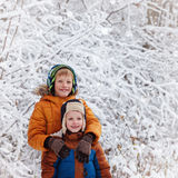 Two little children, boy brothers playing outdoors during snowfall. Active leisure with children in winter on cold days Royalty Free Stock Images
