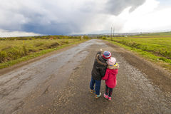 Two little children boy and girl walking on a road Stock Images