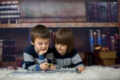 Two little children, boys, reading a book with magnifying glass. At home in front of the library, lying down on the floor Stock Photos