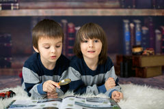 Two little children, boys, reading a book with magnifying glass. At home in front of the library, lying down on the floor Stock Photo