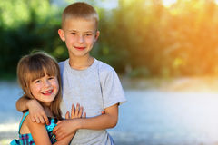 Two little children brother and sister together. Girl in dress h Royalty Free Stock Photography