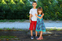 Two little children brother and sister together. Girl in dress h Royalty Free Stock Images