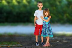 Two little children brother and sister together. Girl in dress h. Ugging boy. Family relations concept Royalty Free Stock Photos