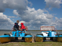 Two little children on a catamaran observing nature. Two little children sitting on a catamaran and observing nature Stock Image