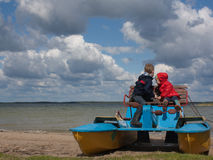 Two little children on a catamaran observing nature. Two little children sitting on a catamaran and observing nature Royalty Free Stock Image