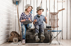 Two little children on chest prepare bait on rod. Two little children sitting on big old chest prepare bait on rod for fishing Royalty Free Stock Photography