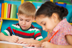 Two little children drawing at kindergarten Stock Images