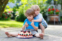Two little children having fun together with big birthday cake Royalty Free Stock Image