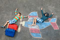 Two little children, kids boys having fun with with airplane picture drawing with colorful chalks on asphalt. Friends. Painting with chalk and going on royalty free stock photos