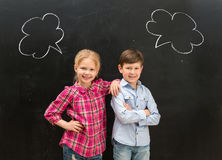 Two little children with phrase clouds on the blackboard stock photos