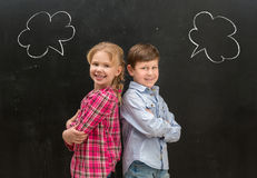 Two little children with phrase clouds on the blackboard stock photo