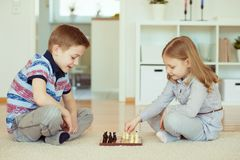 Two little children playing chess at home Royalty Free Stock Photo