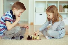 Two little children playing chess at home Royalty Free Stock Photos