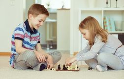 Two little children playing chess at home Stock Photos