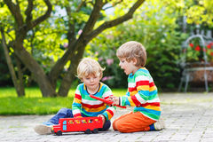 Two little children playing with red school bus Royalty Free Stock Photography