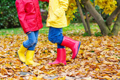 Two little children playing in red and yellow rubber boots in autumn park. In colorful rain coats and clothes. Closeup of happy kids dancing and walking through Royalty Free Stock Photo