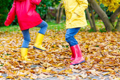 Two little children playing in red and yellow rubber boots in autumn park. In colorful rain coats and clothes. Closeup of happy kids dancing and walking through Royalty Free Stock Image