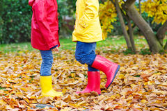 Two little children playing in red and yellow rubber boots in autumn park. In colorful rain coats and clothes. Closeup of happy kids dancing and walking through Stock Photos