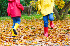 Two little children playing in red and yellow rubber boots in autumn park. In colorful rain coats and clothes. Closeup of happy kids dancing and walking through Royalty Free Stock Photos
