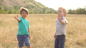Two little boys waving their hands at sunset. Two little children are playing in the suburban park at sunset, they are waving their hands looking at the camera stock footage