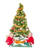 Two little children playing  under christmas tree Stock Photos