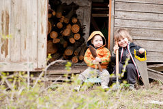 Two little children sit near a shed. With garden tools Stock Photo