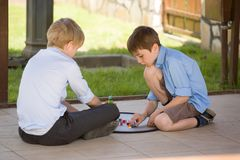 Two little children sit and play with brick game together outdoor at terrace. royalty free stock image