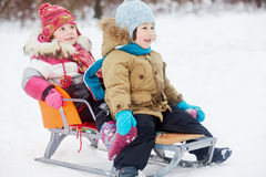 Two little children sit in sled. In winter park Stock Photography