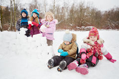 Two little children sit on snow and another three stand aside Royalty Free Stock Photos