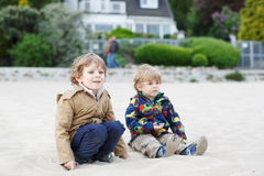 Two little children sitting on beach of river Elbe and playing t Stock Image