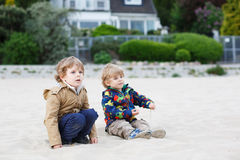 Two little children sitting on beach of river Elbe and playing t Royalty Free Stock Image