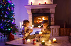 Two little children sitting by a fireplace at home on Christmas Stock Images