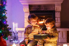 Two little children sitting by a fireplace at home on Christmas Royalty Free Stock Photography