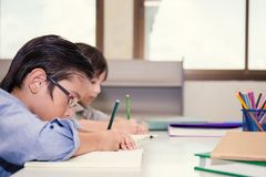 Two little children sitting hand holding pencil and coloring picture Stock Photo