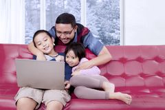 Two children watch a movie with their father. Two little children sitting on the sofa while watching a movie on a laptop with their father Stock Photography