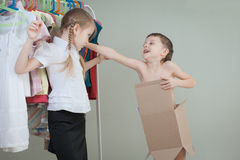 Two little children standing near a hanger with clothes at home Stock Images