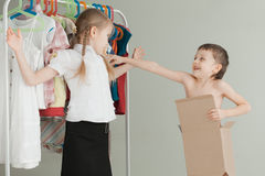 Two little children standing near a hanger with clothes at home Stock Photo