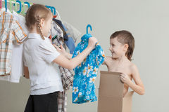 Two little children standing near a hanger with clothes at home Royalty Free Stock Photo